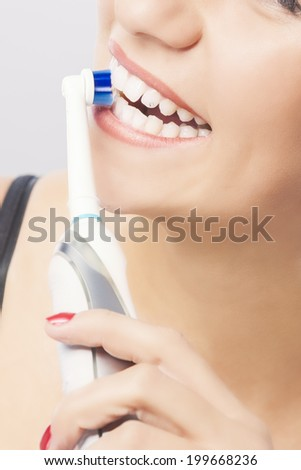 Dental Hygiene: Blond Woman Mouth Closeup while Brushing Teeth with Electric Toothbrush. Vertical Image - stock photo