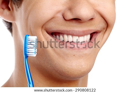Dental hygiene concept with close up of male smile with healthy teeth and blue toothbrush - stock photo
