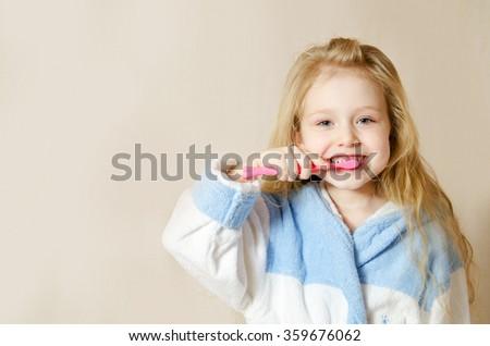 dental hygiene. happy little girl brushing her teeth - stock photo