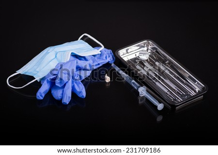 Dental instruments with mask and extracted tooth on black background - stock photo
