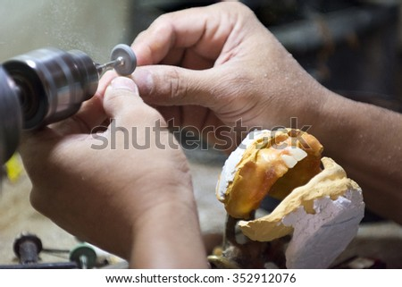 Dental Technician making handmade dental prosthesis in a small shop in the Philippines