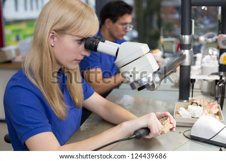 Dental technician producing a prosthesis under a microscope - stock photo