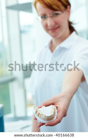 Dental technician showing a ceramic inlay in a lab - stock photo