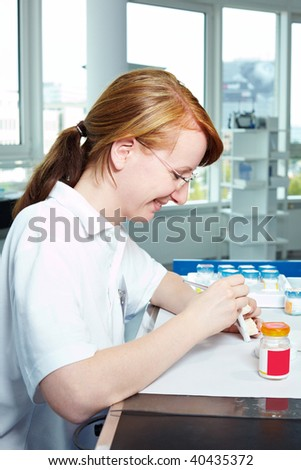 Dental technician working on ceramic inlays in a lab - stock photo
