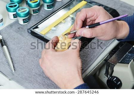 dental technician working on false teeth. table with dental tools.  - stock photo