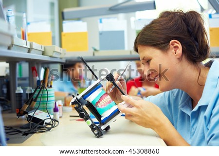 Dental technician working on upper jaw in articulator - stock photo