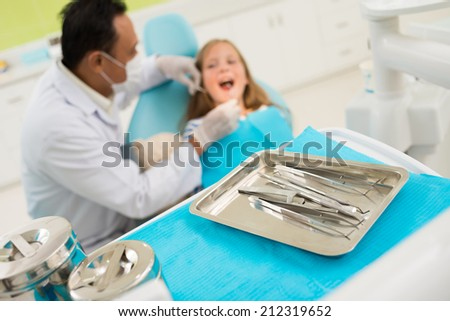 Dental tools on the background of dentist examining patient - stock photo