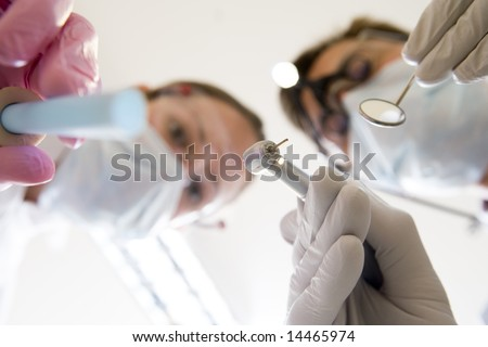 Dentist and assistant holding pick and mirror