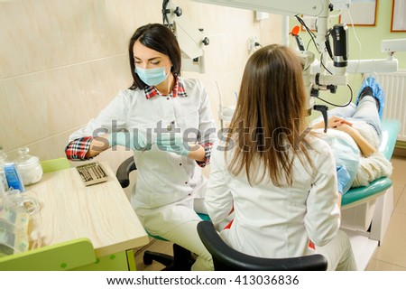 Dentist and assistant in a dental clinic, wearing masks and gloves. Beautiful female dentist holding dental tools getting ready for teeth review with microscope in dentistry. - stock photo