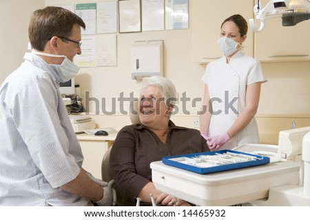 Dentist and assistant in exam room with woman in chair smiling - stock photo
