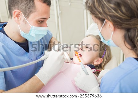 Dentist and dental assistant examining young girl teeth. Dentist is a male, assistant and patient are females. Patient is a young girl, she's smiling and not scared of dentist. - stock photo