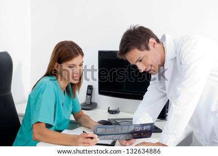 Dentist and female assistant analyzing patient's X-ray report at office desk - stock photo