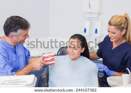 Dentist and nurse explaining to their patient how use toothbrush with a model in dental clinic - stock photo
