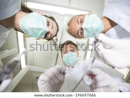 Dentist and nurses from low angle view - stock photo