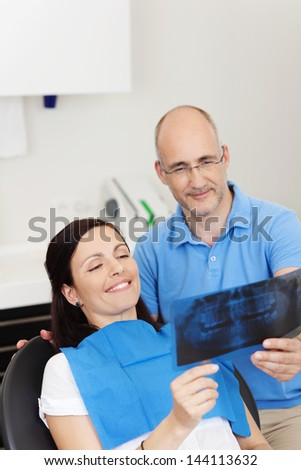 Dentist and patient smiling while looking at Xray in clinic - stock photo