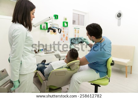 Dentist , Assistant And Patient Looking At Tooth X-Ray - stock photo