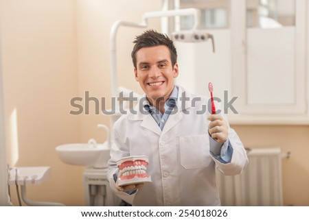 Dentist brushing teeth on dental model. Smiling dentist holding toothbrush in hand - stock photo