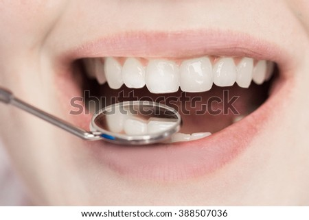 Dentist checking woman's teeth - stock photo