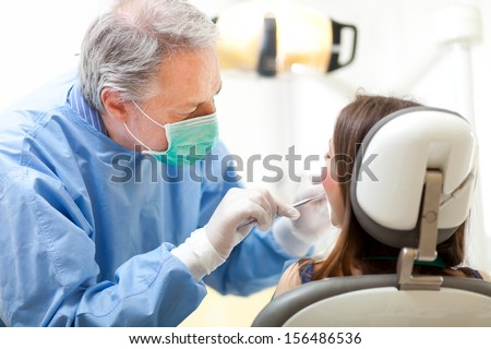 Dentist curing a female patient  - stock photo