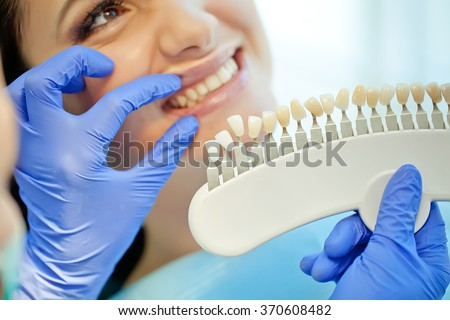 Dentist curing a woman patient in the dental office in a pleasant environment. There are specialized equipment to treat all types of dental diseases in the office.  - stock photo
