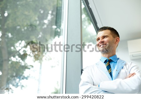 Dentist Doctor Stands Near Window and Thinks about Clinic Future - stock photo