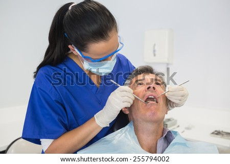 Dentist examining a patient with tools in dental clinic - stock photo