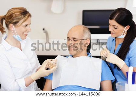 Dentist explaining teeth model to male patient at clinic - stock photo