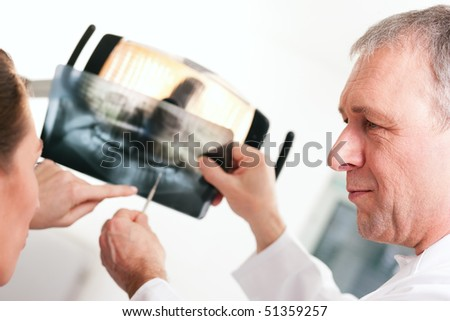 Dentist explaining the details of a x-ray picture to his patient, focus on eyes of doctor - stock photo