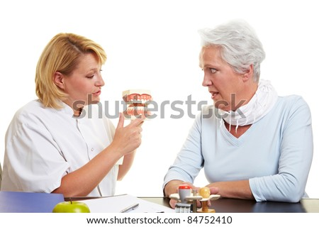 Dentist explaining work to senior woman on teeth model - stock photo