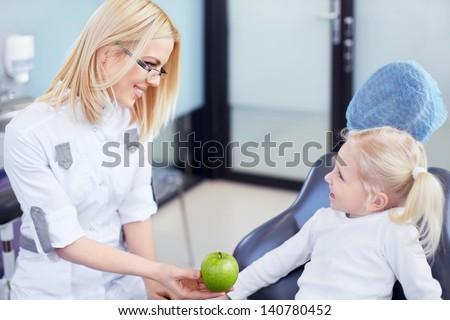 Dentist gives little girl green apple - stock photo