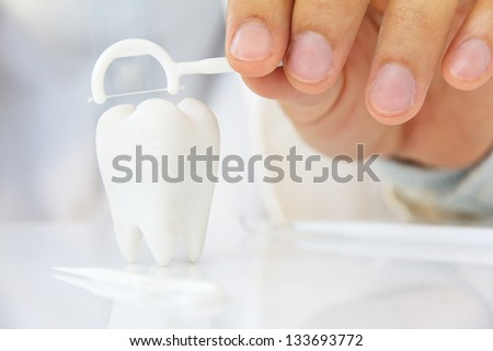 dentist holding dental floss with molar,dental concept - stock photo