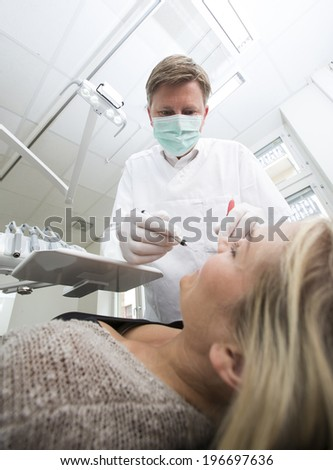 Dentist in action from low angle view - stock photo