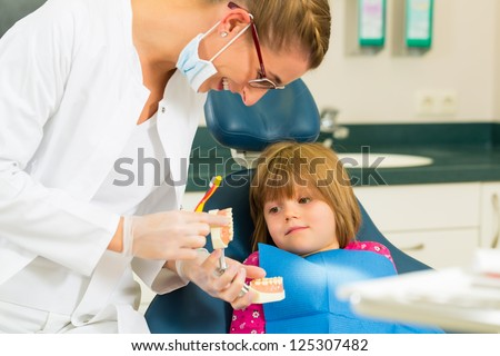 Dentist in surgery holds denture and explains a child patient with a toothbrush - stock photo
