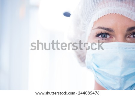 Dentist in surgical mask and cap looking at camera at the dental clinic - stock photo