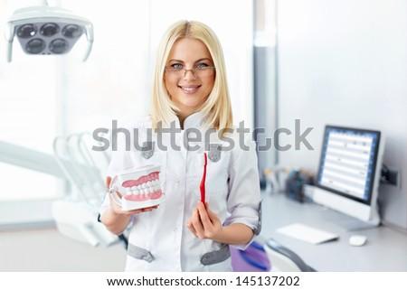 Dentist in uniform in a dental clinic - stock photo