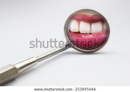 Dentist mirror with reflection of teeth in a white background - stock photo