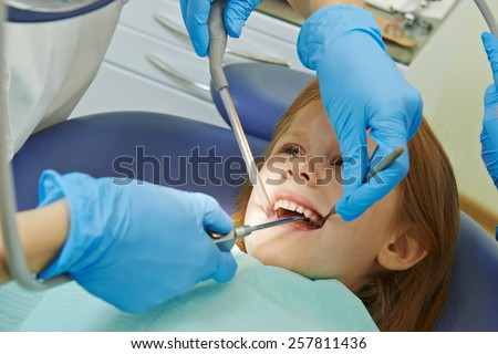 dentist orthodontist female doctor hands with dental tools during child care at clinic - stock photo