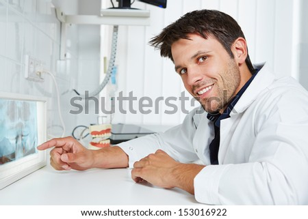 Dentist pointing with his finger at x-ray image in dental practice - stock photo