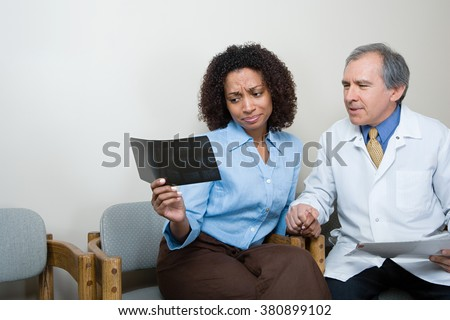 Dentist showing patient x ray - stock photo