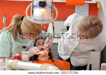 Dentist student drill  tooth of a young patient with professor looking - stock photo