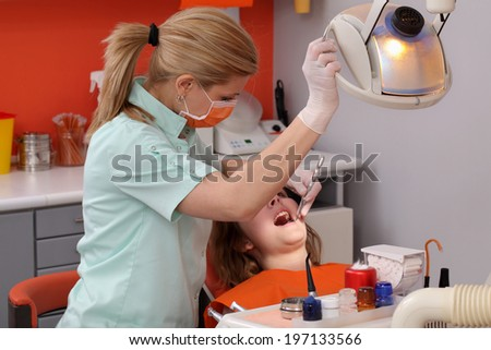 Dentist student examine  tooth of a young patient using light, real people - stock photo