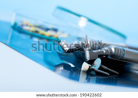 dentist tools. mirror, curling on a blue background - stock photo