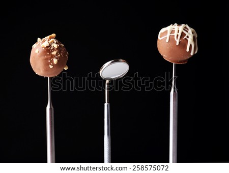 Dentist tools with sweets isolated on black - stock photo