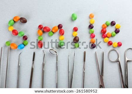 Dentist tools with sweets makes smile word on light background - stock photo