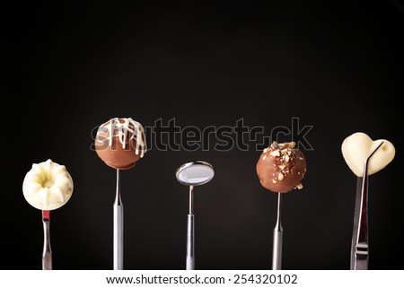 Dentist tools with sweets on dark background - stock photo