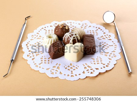 Dentist tools with sweets on lacy napkin on beige background - stock photo