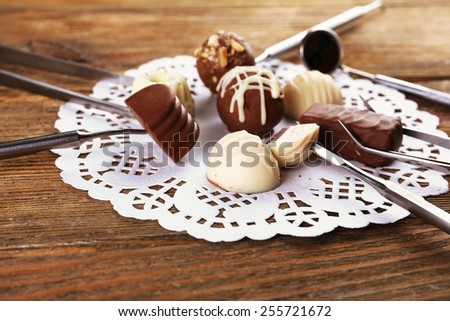 Dentist tools with sweets on lacy napkin on wooden background - stock photo