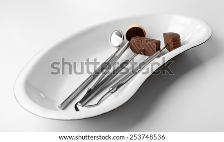 Dentist tools with sweets on tray isolated on white - stock photo