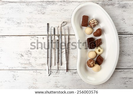 Dentist tools with sweets on tray on wooden background - stock photo