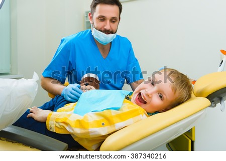 Dentist treats teeth of patient in dental clinic - stock photo